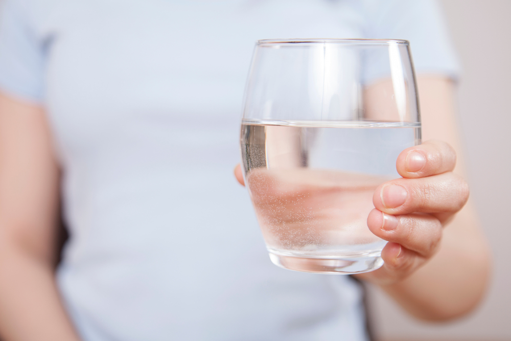 Woman is hand holding drinking water on gray background - Image( Busra Ispir)S