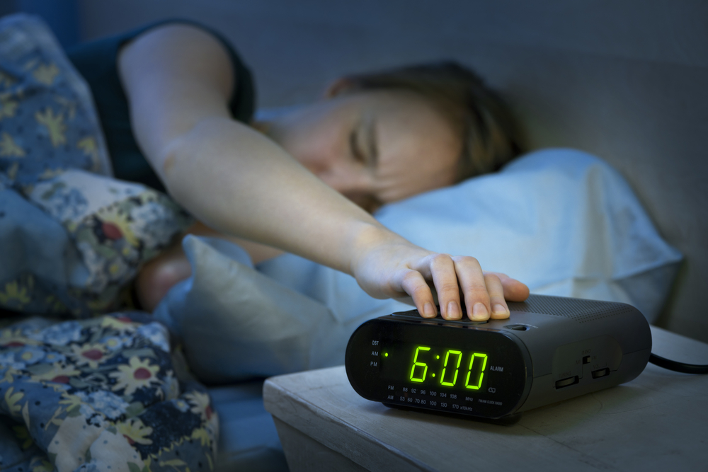 Young woman pressing snooze button on early morning digital alarm clock radio - Image( Elena Elisseeva)s