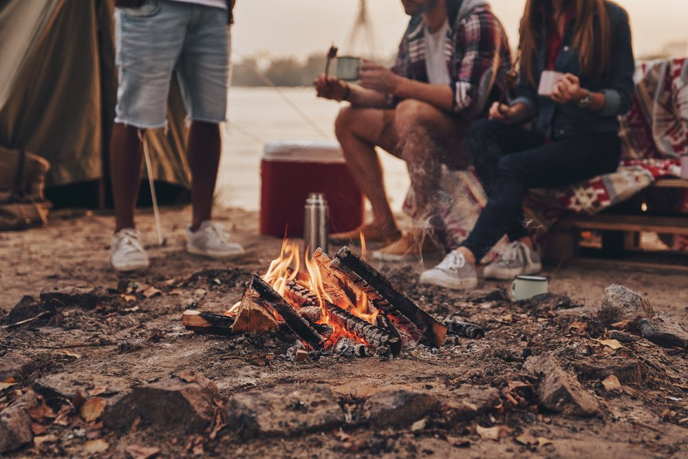 Great warm evening. Close up of young people eating roasted marshmallows while camping near the lake - Image(G-Stock Studio)s