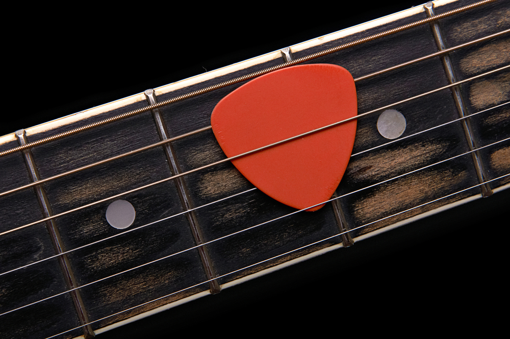 Orange guitar pick on the fingerboard - Image( Oleg Belov)s