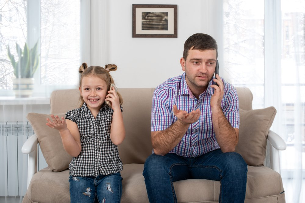 Studio shot of a daughter and dad sitting on the sofa at home and talking on the phone the same way(Rozochka)s