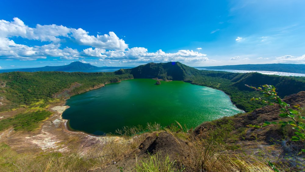 View of cones of Taal Volcano and the wind ruffled emerald green water in the Lake Taal on a sunny day in Tagaytay, Philippines. - Image(Spectral-Design)s