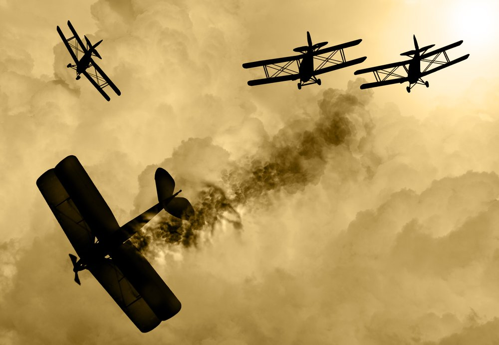 Vintage world war one biplanes and engaged in a dog fight in a cloudy sky. One had success in shooting down the enemy plane( Keith Tarrier)s