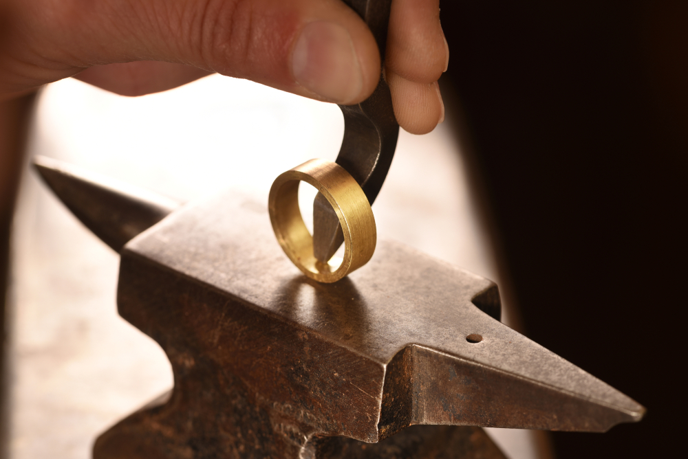 hand of a goldsmith punches a hallmark into a golden ring on an anvil, close up with copy space, focus, narrow depth of field - Image(Maren Winter)S