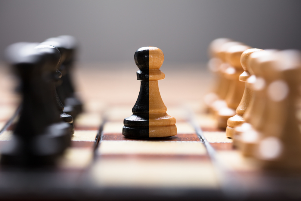 Closeup of double color pawn amidst other chess pieces on board game - Image(Andrey_Popov)s