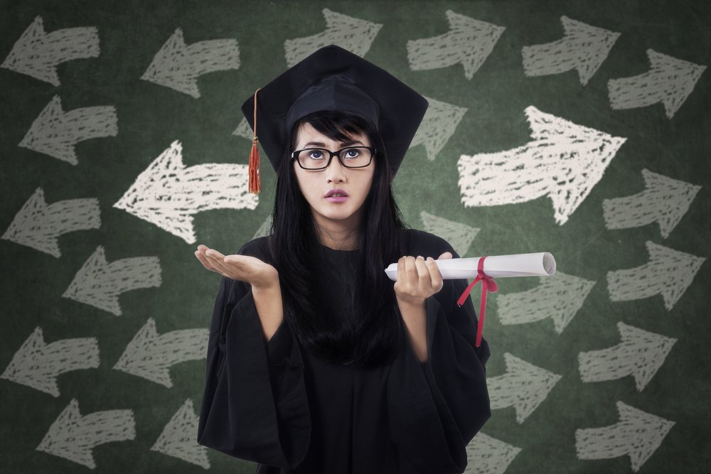 Confused young female in graduation gown with arrow symbol on the blackboard - Image( Creativa Images)s