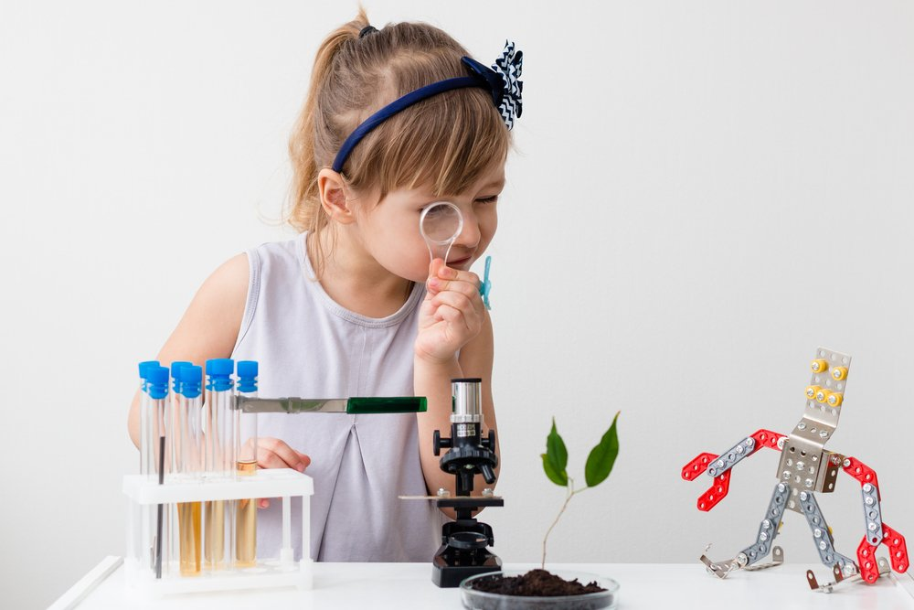Little girl is behind the desk. Microscope and the tree are near her. Little robot. E-learning. Stem education. - Image(AlesiaKan)s