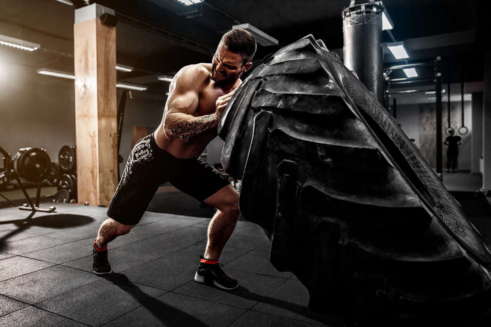 Shirtless man flipping heavy tire at gym - Image( Oleksandr Zamuruiev)s