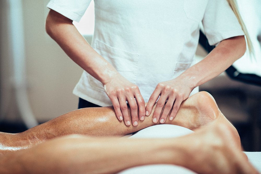 Sports Massage. Massage therapist working with patient, massaging his calves. Toned image. - Image(Microgen)s