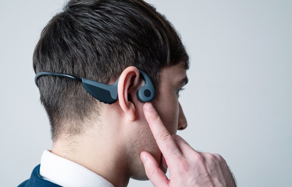 Young man wearing a bone conduction headphones(metamorworks)S