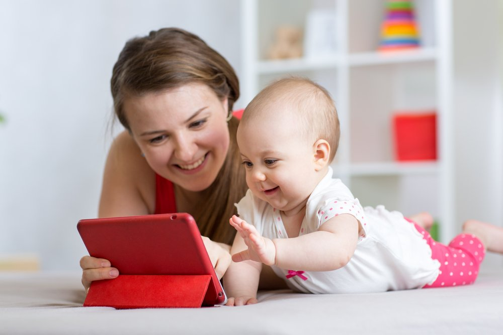 mother and baby with tablet on floor at home. Woman and child girl relaxing at tablet computer( Oksana Kuzmina)s