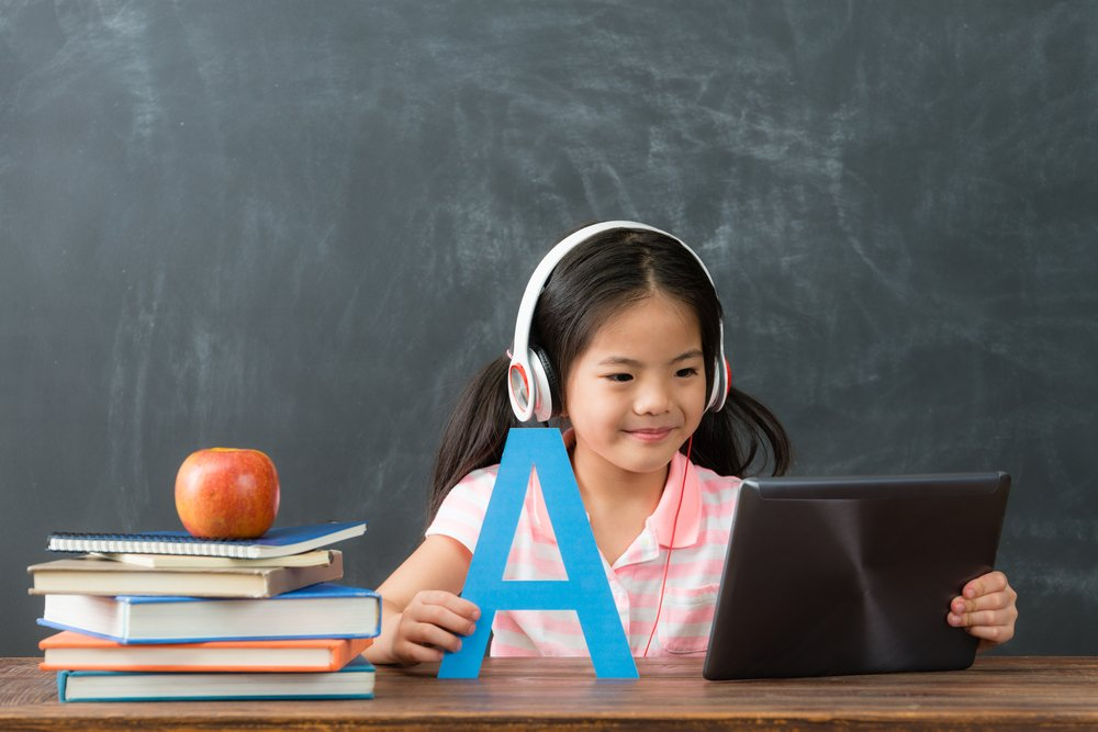 smiling young female kid children using digital tablet pad watching online e-learning video to studying english in chalkboard background. - Image(By PR Image Factory)s