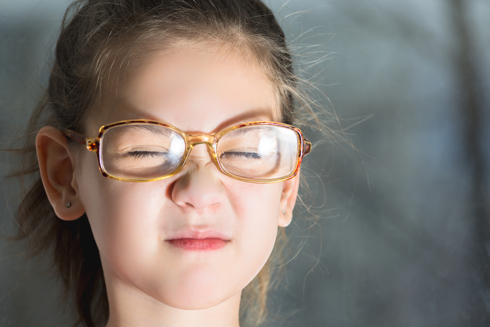Beautiful child with glasses squinting from the light(Tagwaran)s