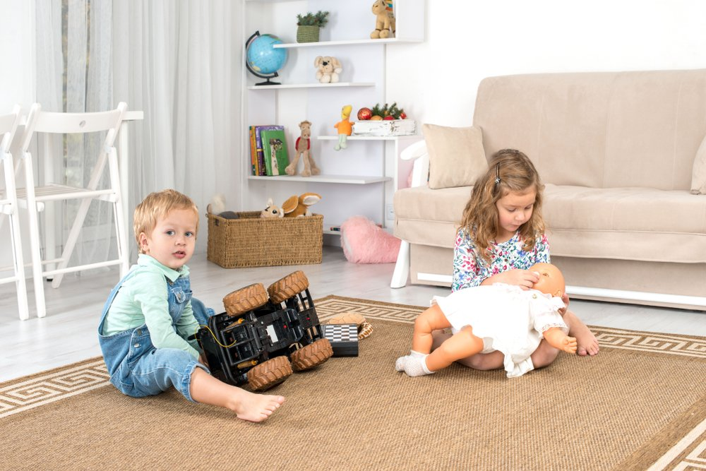 Little children, a boy and a girl, sit on the floor on a rug in the room at home and play(Rozochka)S