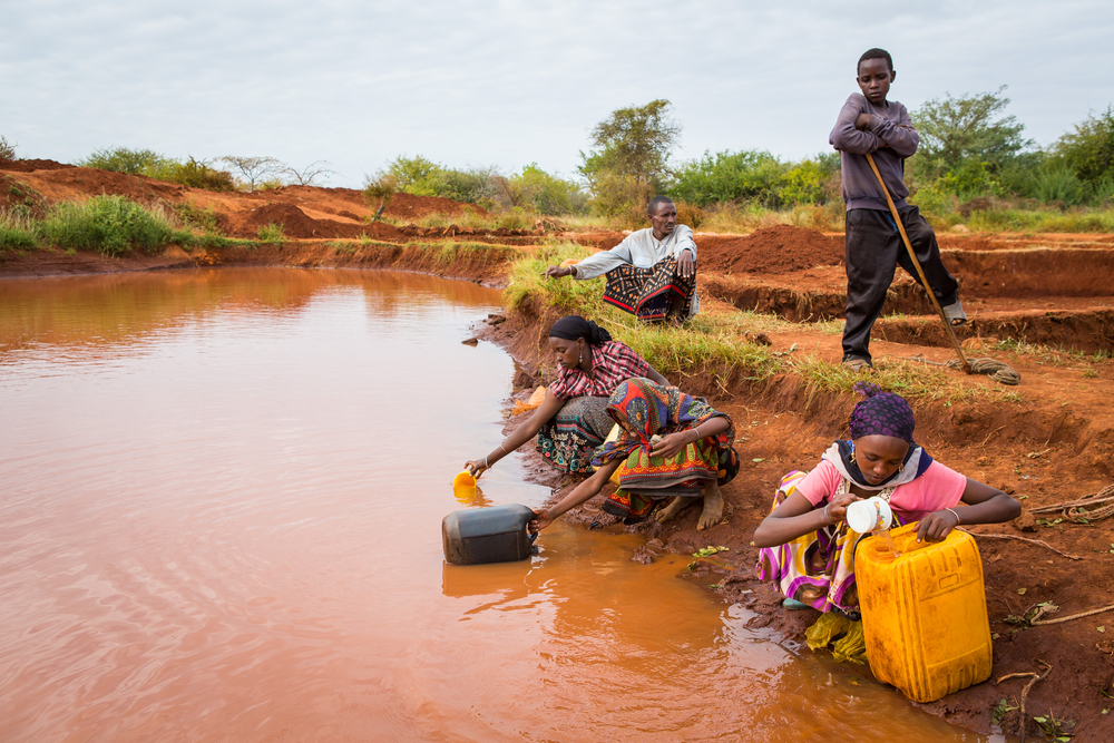 Women and young village girls collect water from a rain water pool which is purified before use with tablets(Martchan)s