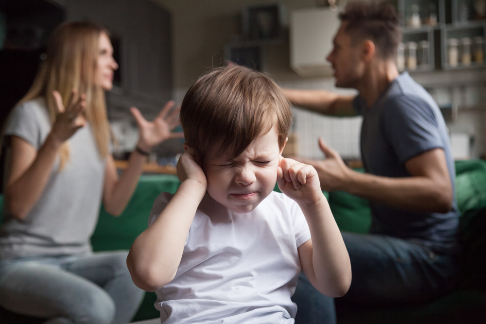 Frustrated kid son puts fingers in ears not listening to noisy parents arguing(fizkes)s