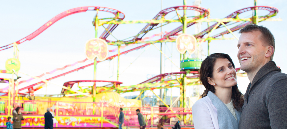 Panoramic view of beautiful tourist couple visiting colorful amusement park with roller coaster ride(MJTH)s