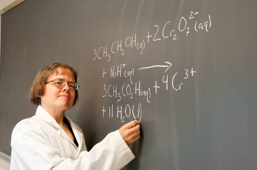 A woman chemistry instructor writes out a chemical equation on a chalk board(Erika J Mitchell)S
