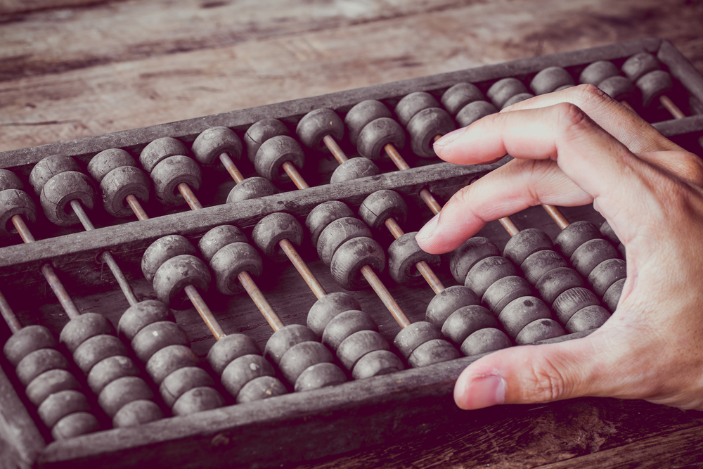 Vintage tone of Man's hands accounting with old abacus and hold electronic calculator(Patty Chan)s