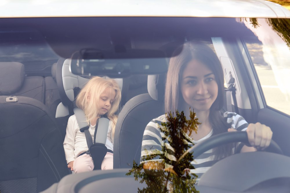 Young woman driving car with small girl in safety seat( Africa Studio)S