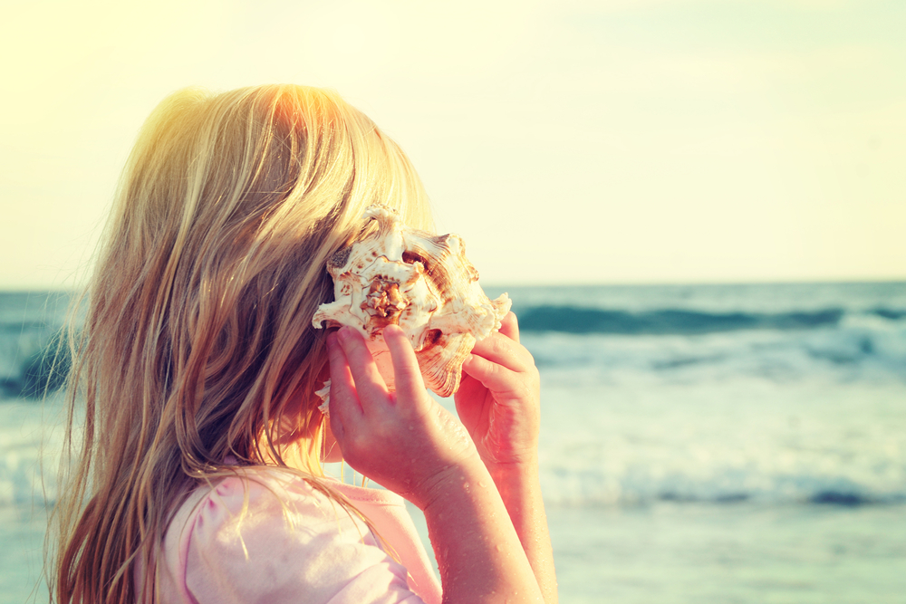 Happy little girl listen to seashell at the beach(Guschenkova)s