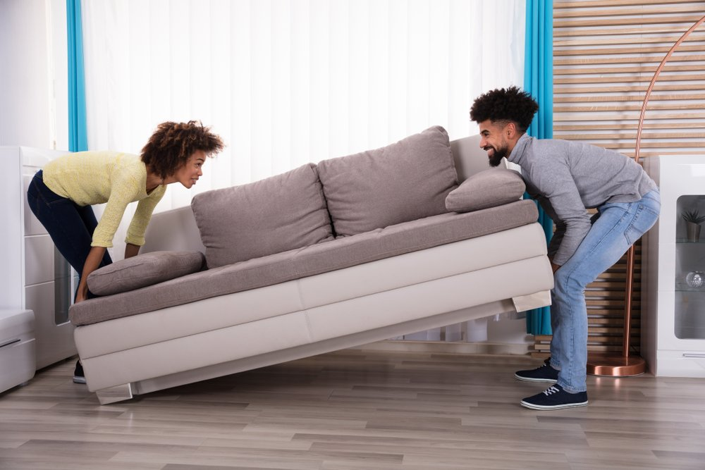 Side View Of Young Smiling Couple Lifting Sofa In Living Room(Andrey_Popov)S