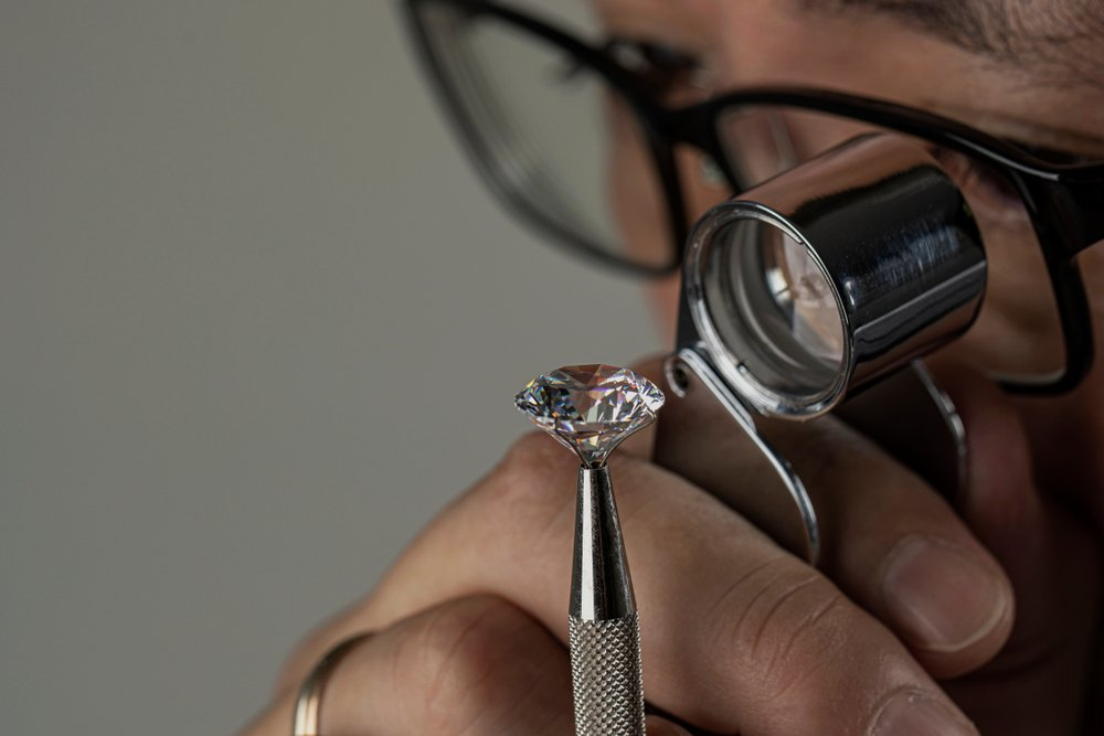Man jeweller examines polished diamond through magnifier(EgolenaHK)s
