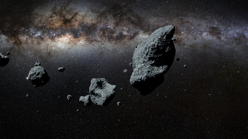 a swarm of asteroids in front of the Milky Way galaxy