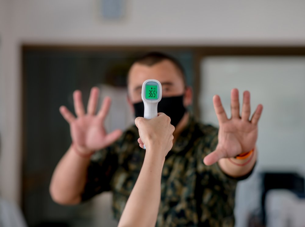 Close-up of a protective masked man ready to be used with an infrared forehead thermometer(JETACOM AUTOFOCUS)s