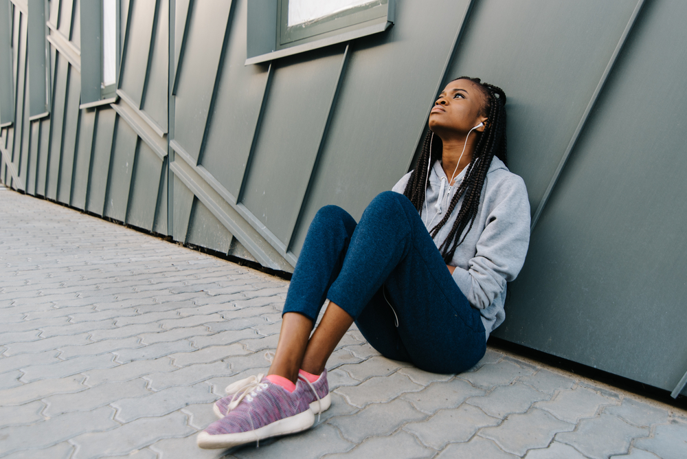 Depression teen african american girl listening to music and sitting lonely looking up(Andrii Kobryn)s