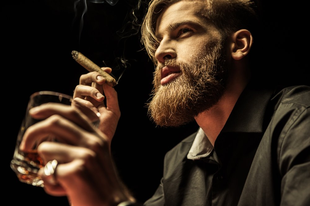 Handsome bearded man holding glass of whisky and smoking cigar(LightField Studios)s