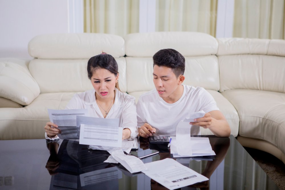 Picture of young couple looks stressed while checking their high expenses(Creativa Images)s
