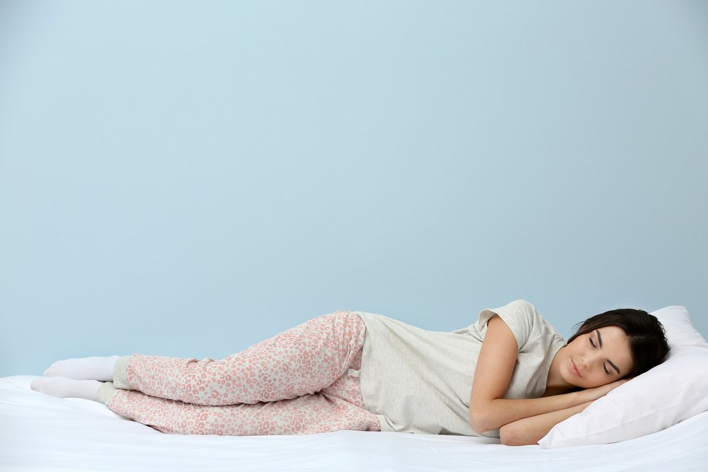 Young woman in pajamas sleeping on bed on blue background(Africa Studio)S