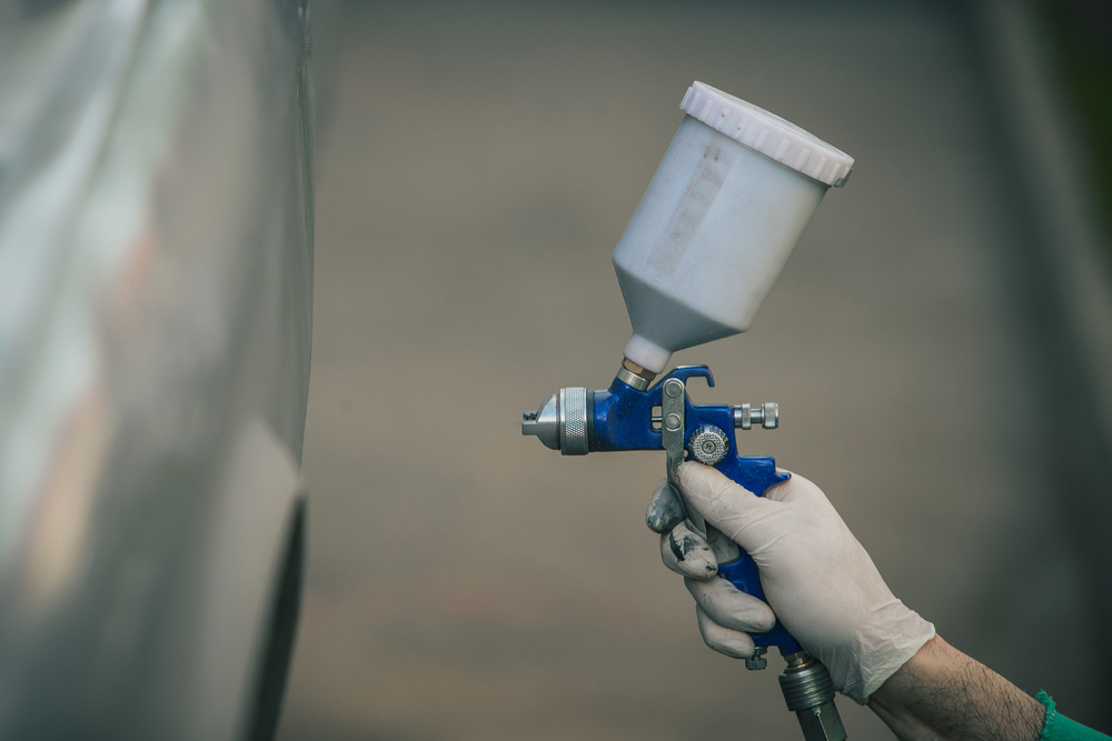 Caucasian man is spraying color with a compressed air paint gun on the vintage car as a restoration project(Anze Furlan)s