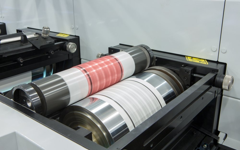 Flexography printing process on in-line press machine. Photopolymer plate stuck on printing cylinder(boitano)s