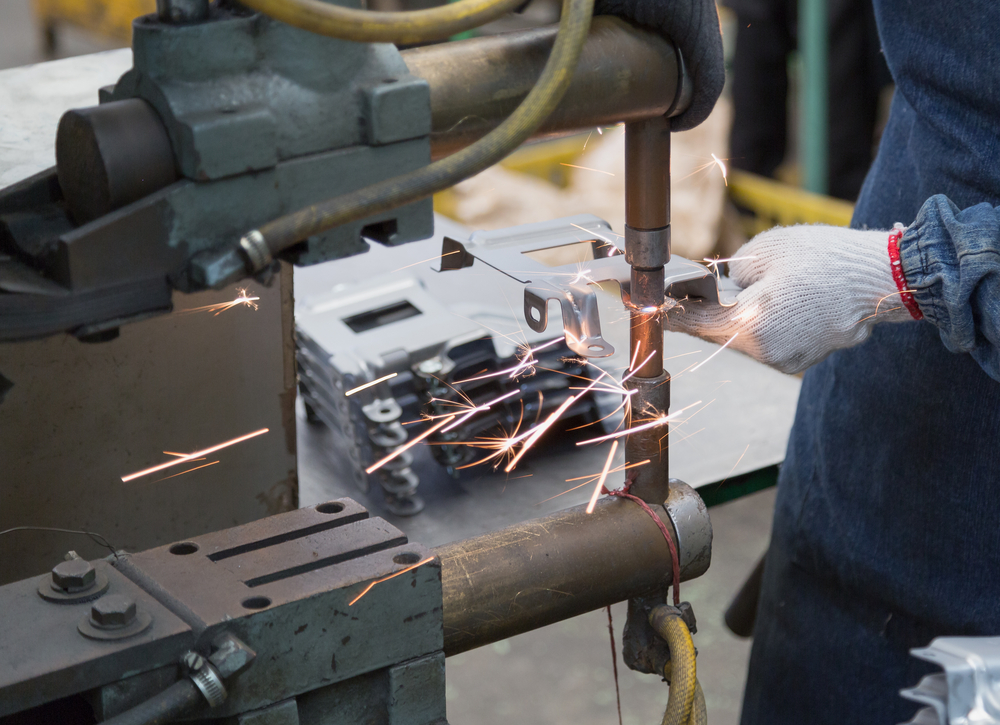 Operator is working with spot welding process for automotive part(sondoggie)s