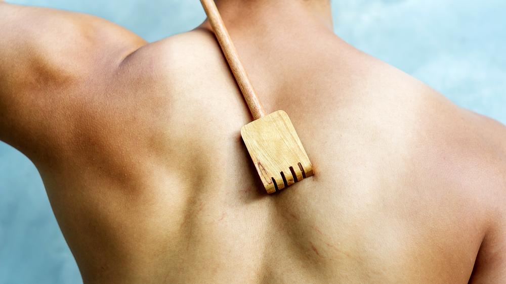 Man scratching his back with a wooden backscratcher(Supaleka_P)s