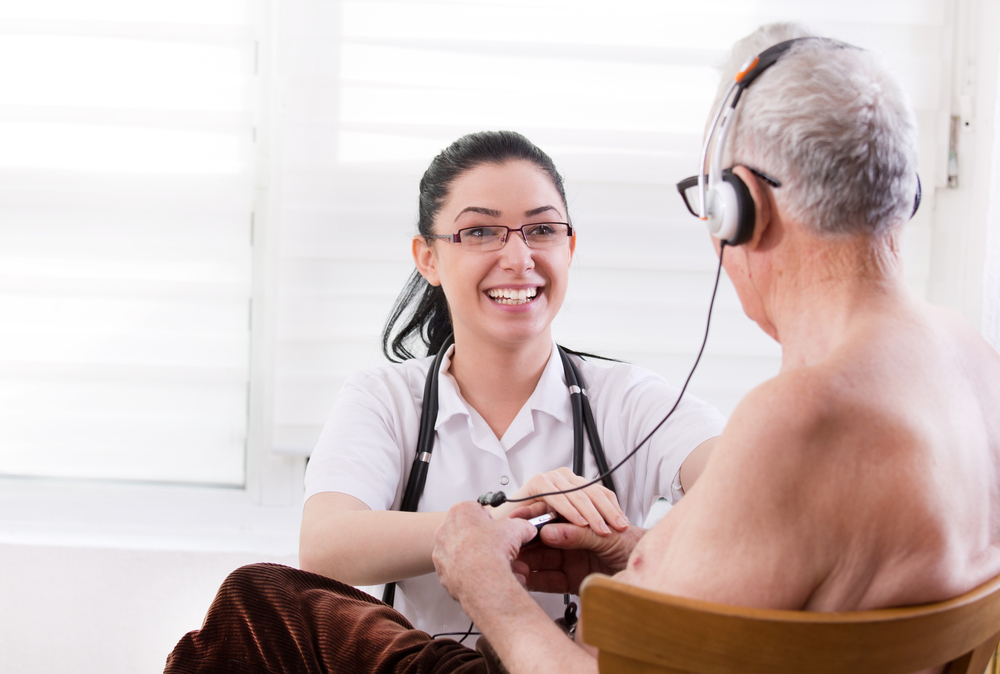 Smiling young nurse taking care about senior man with headset(Budimir Jevtic)s