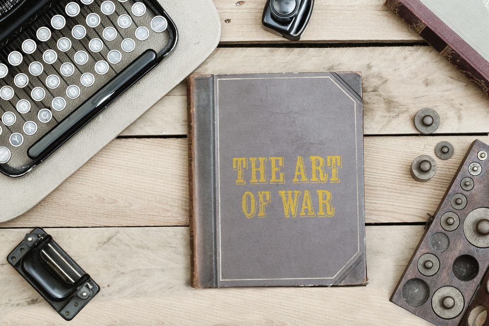 The Art of War text on cover of old book on office desk with vintage type writer machine(MichaelJayBerlin)S