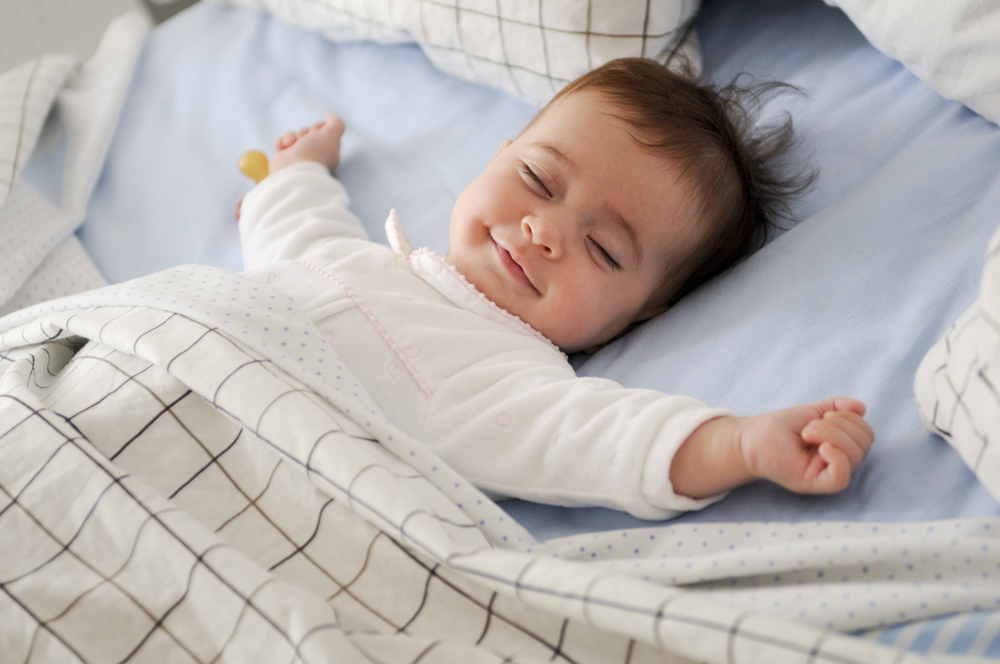 Smiling baby girl lying on a bed sleeping on blue sheets(javi_indy)S