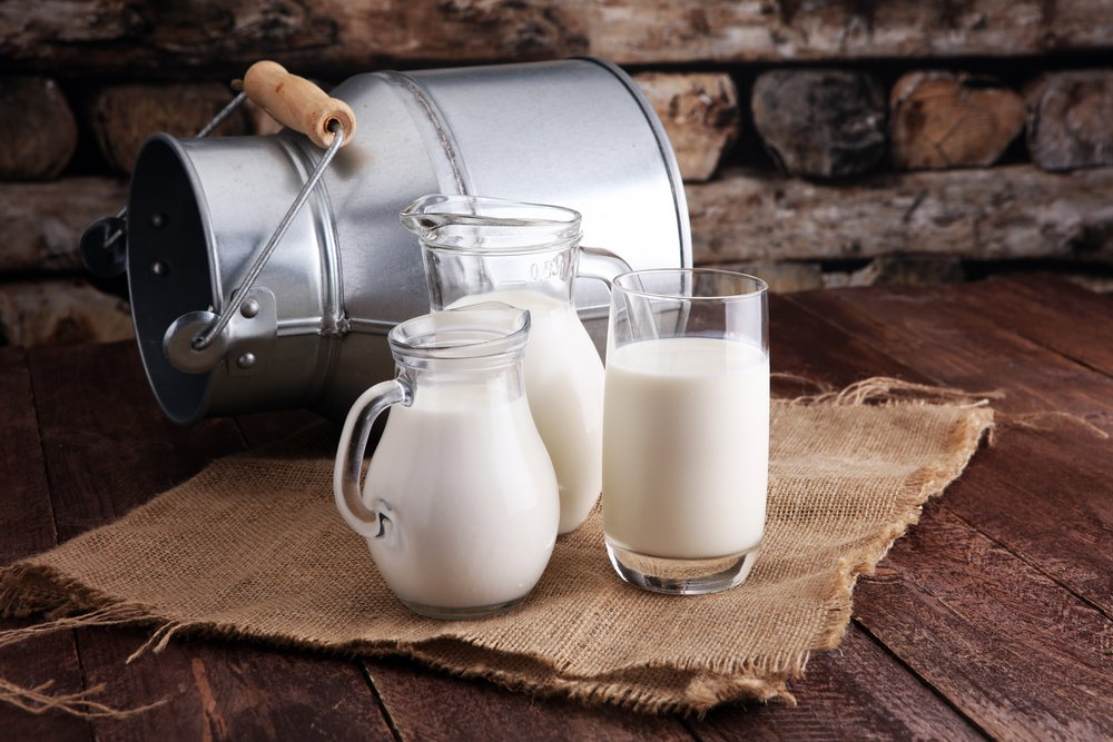 A jug of milk and glass of milk on a wooden table(beats1)s