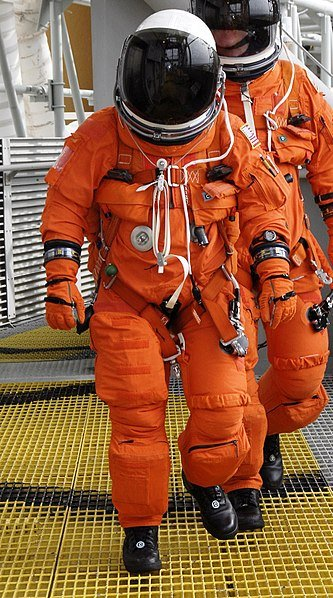 dressed in their helmets and launch-and-entry spacesuit