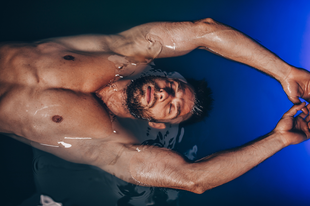 Handsome beard man floating in tank filled with dense salt water used in meditation(hedgehog94)S