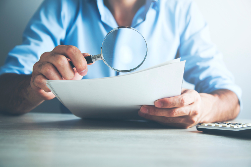 Businessman looking through a magnifying glass to documents(Tiko Aramyan)s