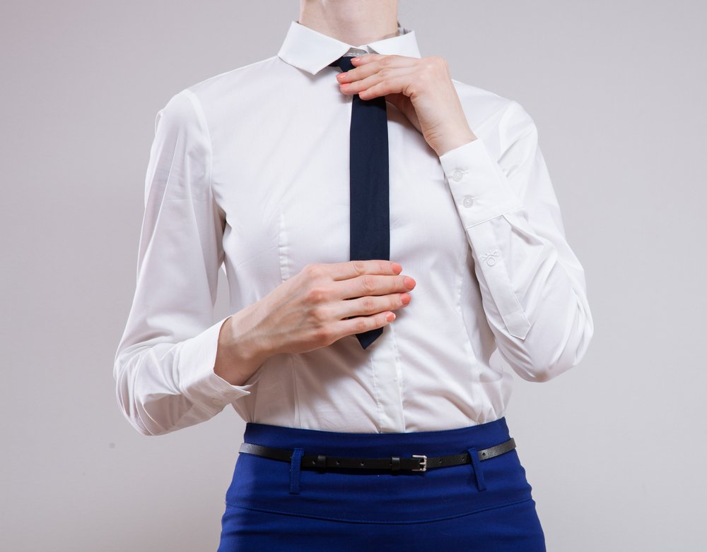 Unrecognizable businesswoman sets the necktie on neutral background(Maryna Pleshkun)S