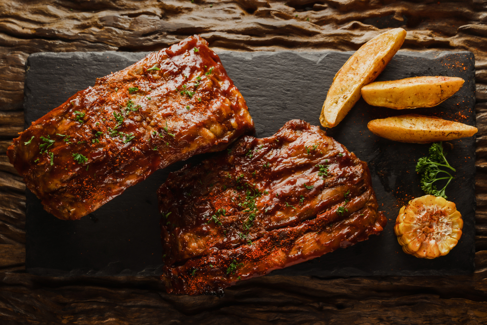 food background of BBQ barbeque pork ribs served with potato fried and baked corn(Mongkolchon Akesin)s