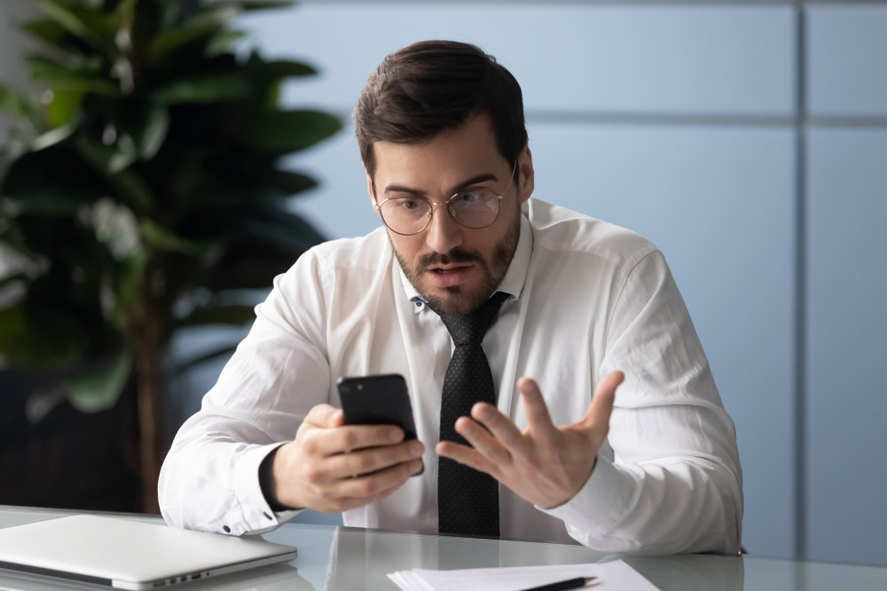 Businessman holds gadget feels annoyed with broken phone(fizkes)s