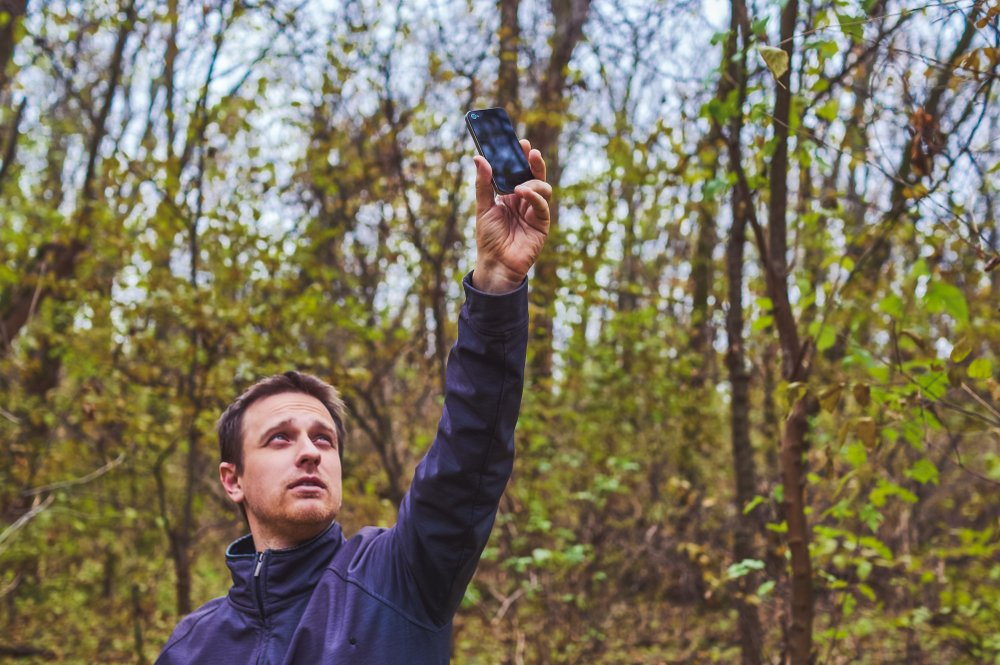 Man with his mobile smart phone searching for reception signal in the forest(Alrandir)s