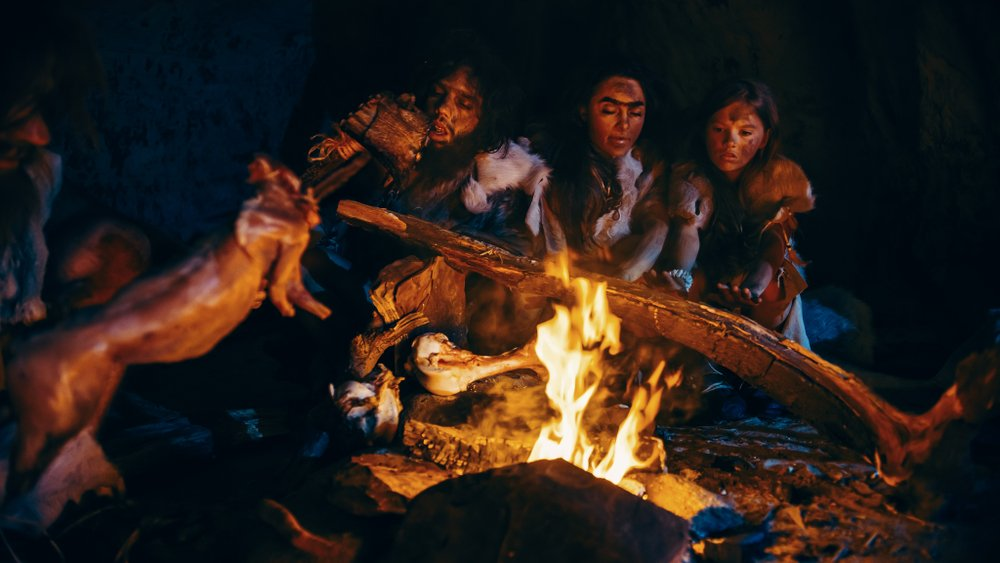 Neanderthal or Homo Sapiens Family Cooking Animal Meat over Bonfire and then Eating it(Gorodenkoff)S