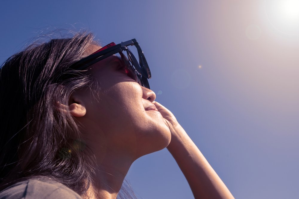 Woman is looking on solar eclipse through three sunglasses. Sun eclipse concept(Stocker plus)s